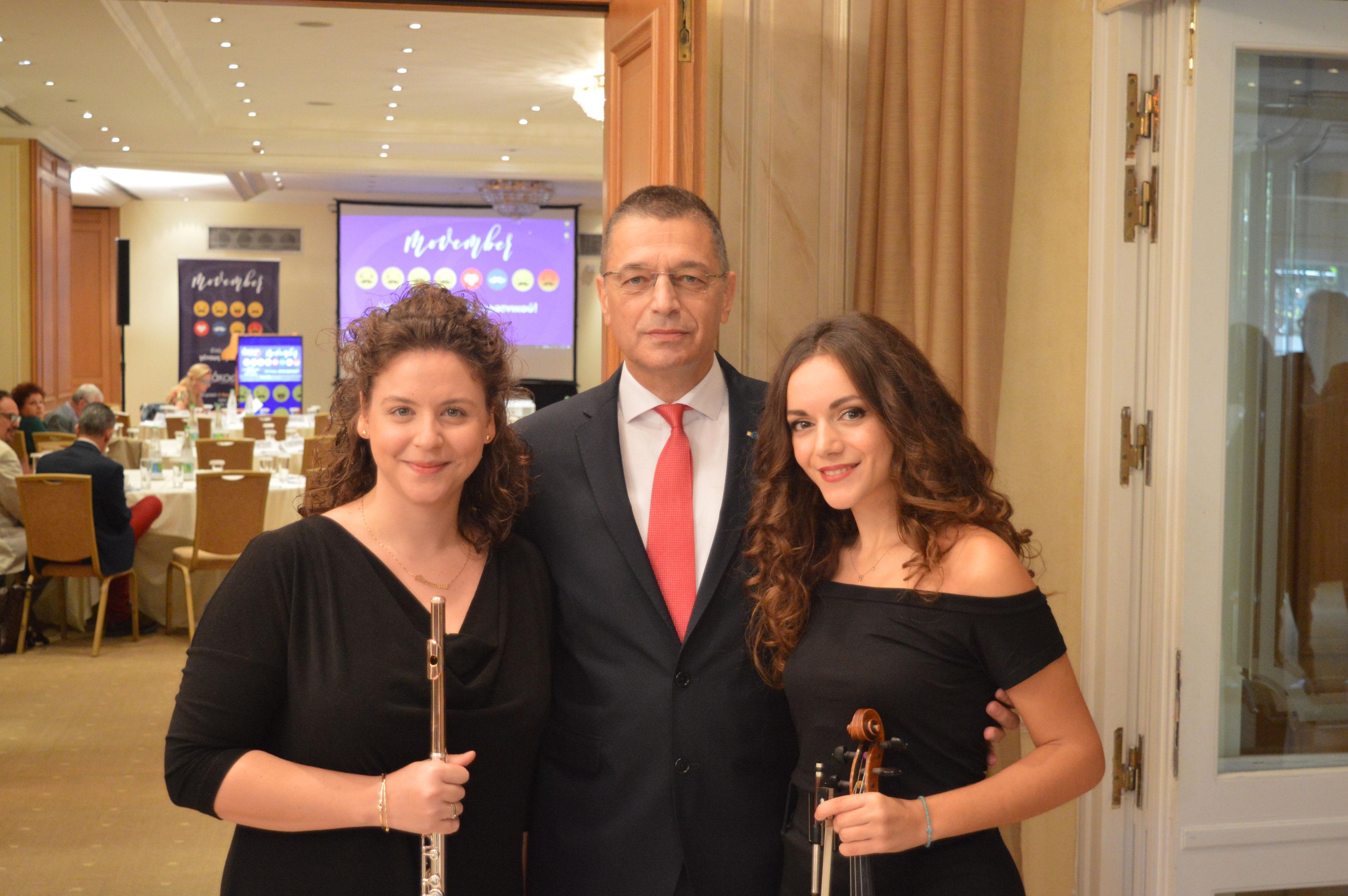 Ο υφυπουργός Άμυνας Αλκιβιάδης Στεφανής πλαισιωμένος από τη φλαουτίστα Δέσποινα Σπαή και τη βιολονίστα Στέλλα Ζιοπούλου.